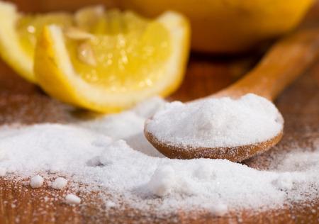 agua con gas: bicarbonato de sodio (bicarbonato de sodio) en una cuchara de madera y lim�n