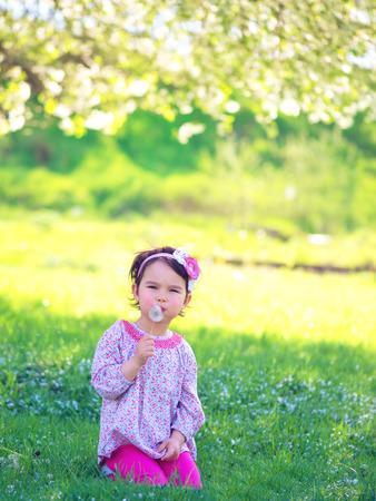 blowing dandelion: Happy child blowing dandelion outdoors in spring park