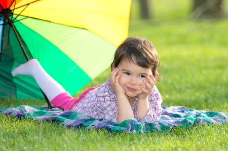 rainbow umbrella: little girl with a rainbow umbrella in park