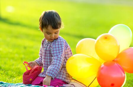 ittle: ittle girl sitting on the grass with balloons