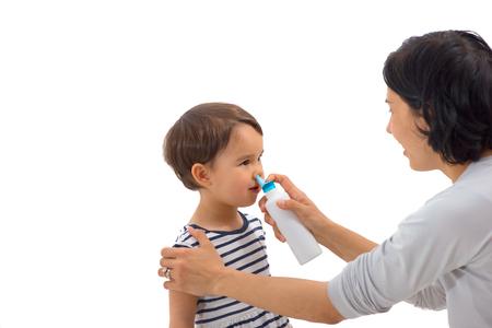parent of a girl applies a nasal spray