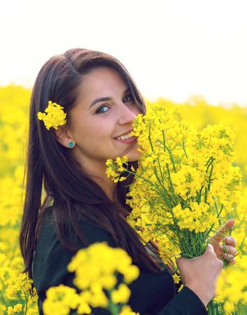 adult rape: Beautiful Woman  holding a bunch of rape flowers. Rape Field. Yellow Field. rapeseed plantation. Canola Field. Girl In Field.