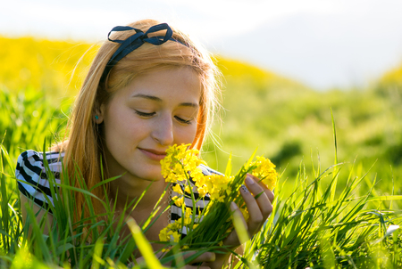 preasure: portrait of beautiful young long-haired woman lying in park and smelling flowers Stock Photo