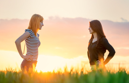 two beautiful girl in the sunset having an argue Stock fotó