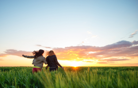 two girl friends running into wheat to the sunset