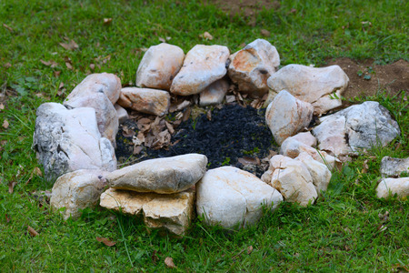 Open fire outdoors. Chic bonfire topped with stones in nature Stock Photo