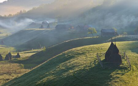 Carpathian rural landscape with a haystack and misty mountains.
