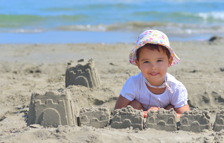 children sandcastle: Little girl at tropical beach making sand castle