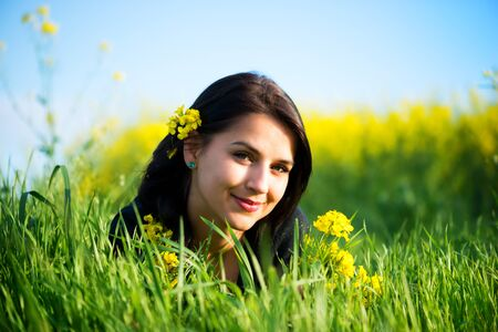 preasure: portrait of beautiful young long-haired woman lying in grass, with colza flowers in backround