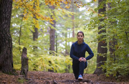 Energetic young woman do exercises outdoors in park to keep their bodies in shape. Fitness concept. Body-building theme. Sport mood. Standard-Bild