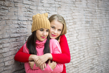 two girls hugging: Two girls hugging and having fun on a background of  brick wall Stock Photo