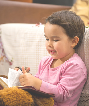 bedtime story: Cute little child girl reading a book