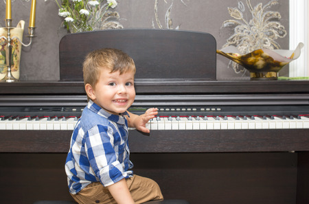 Prodigy: Happy boy playing the piano at home
