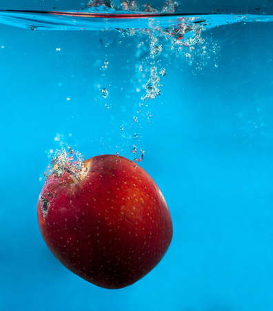 circular blue water ripple: Red apple in water with splash and drops