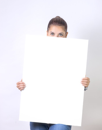over the edge: Banner sign woman peeking over edge of blank empty paper billboard with copy space for text
