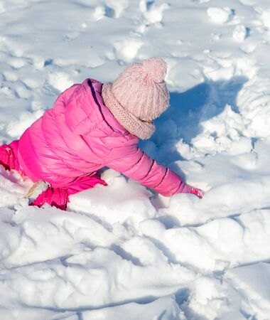 Little girl in snow, playing