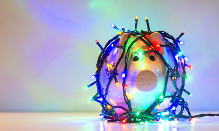 Piggy bank wrapped in Christmas string lights 版權商用圖片 - 73063228