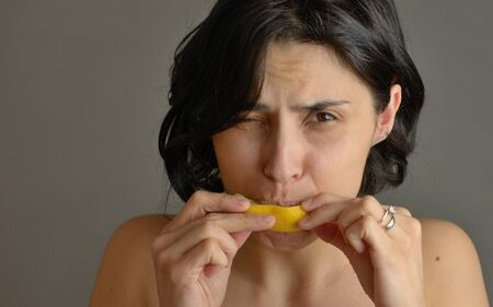 Woman eating lemon and making silly faces Stock Photo