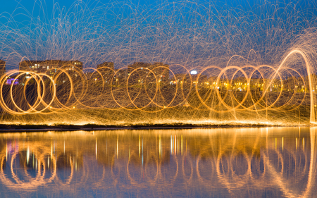 steel wool: Hot Golden Sparks Flying from Man Spinning Burning Steel Wool near River with Water Reflection. Long Exposure Photography using Steel Wool Burning