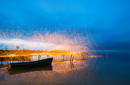steel wool: Freeze light using spinning burning steel wool  near an old boat on the lake