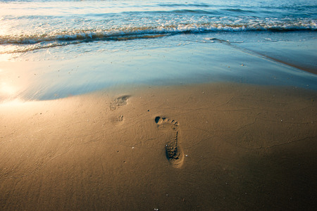 Beach wave and footprints at sunset time