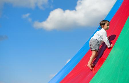 Little girl goes up on rainbow, at playground Standard-Bild