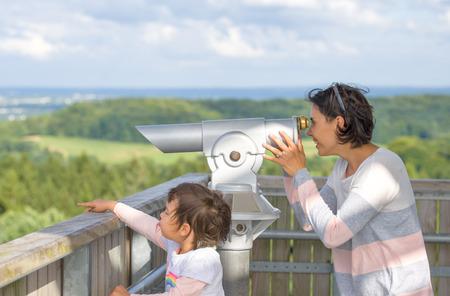 Mother and her daughter looking through a viewing binocular Banco de Imagens