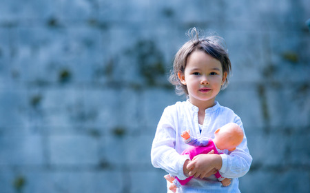 Little girl holding her doll, outdoor