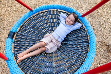 Little girl child sitting on a swing in the garden playground; she has lots of fun Standard-Bild