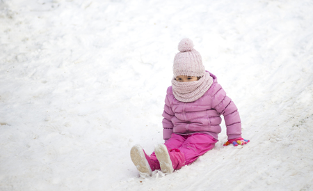 young child playing in the snow