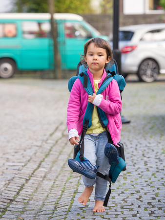 Little child with luggage back walking on the streets in bare feet