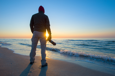 man is photographing a sunrise against the background of the sea.