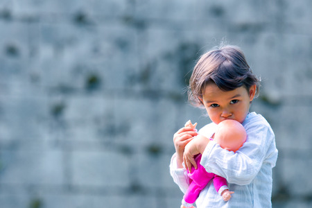 Cute little girl holding and embracing her doll Standard-Bild