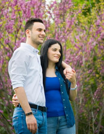 Happy girl and her boyfriend having walk in park