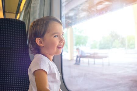 Happy little girl traveling by train