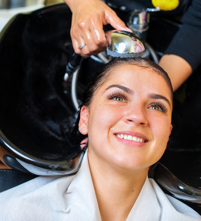Beautiful young woman with hairdresser washing head at hair salon