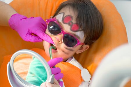 Little cute girl sitting in chair at dentist with sunglasses getting treatment