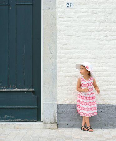 little girl in pink dress and white summer hat outdoor Standard-Bild