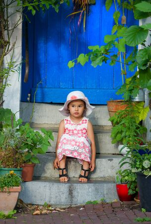 cute smiling little girl sitting on  stairs of house barefoot Standard-Bild