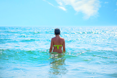 Back view of a pretty young woman on the sea Standard-Bild