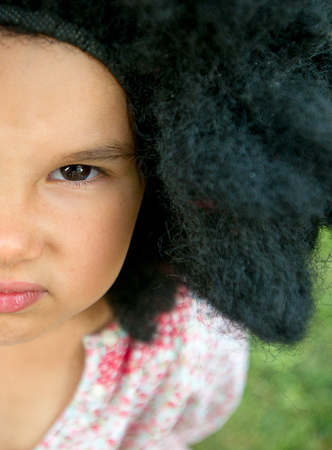 copy space and half face of little girl wearing a big black wig
