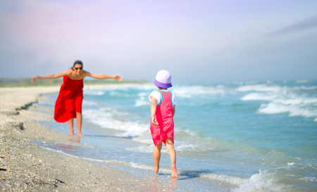 mother with her little girl playing on the seashore Standard-Bild