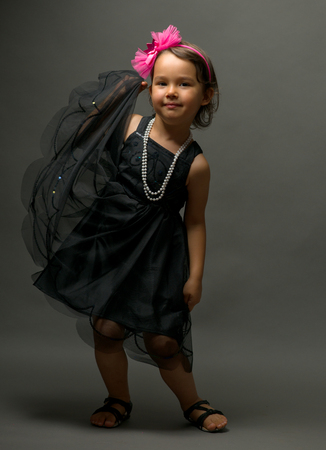 Little cute girl dancing  on gray background
