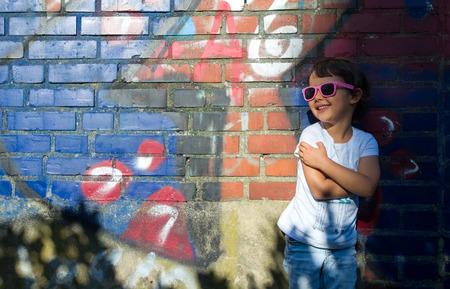 Portret van glimlachend en aardig meisje met erachter brickwall Stockfoto - 94195863