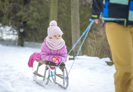 Mother sledding his little girl on an old sled Standard-Bild
