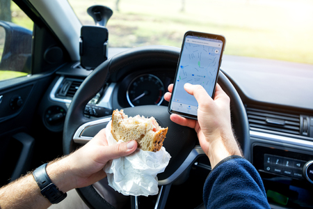 man eating and texting while driving car