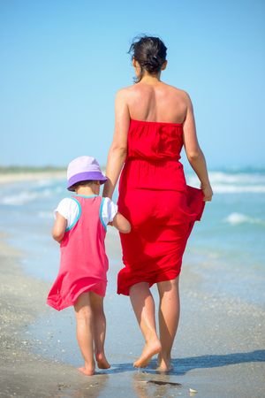 Back view of a mother with her little girl walking on the seashore Standard-Bild - 110837638