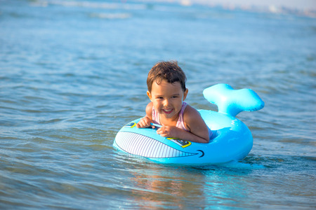 Little girl swimming on inflatable at the sea Standard-Bild - 106318203