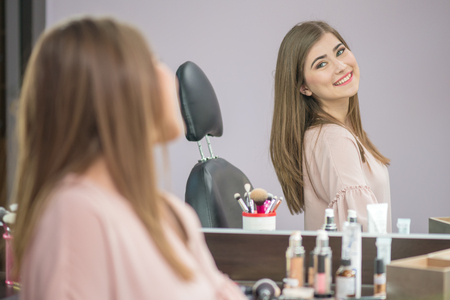 Beautiful woman with hairstyle and makeup looking at the mirror in beauty salon one Standard-Bild - 106318207