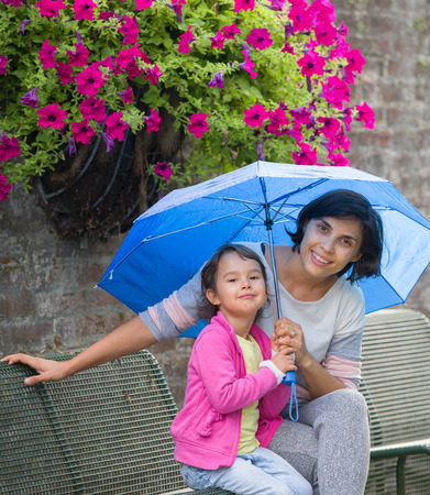mother and daughter on a bench with an umbrella Standard-Bild - 106318251